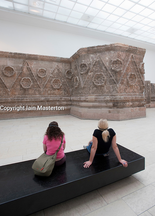 Visitors looking at remains of Palace of Mshatta at Pergamon Museum on Museumsinsel in Berlin Germany