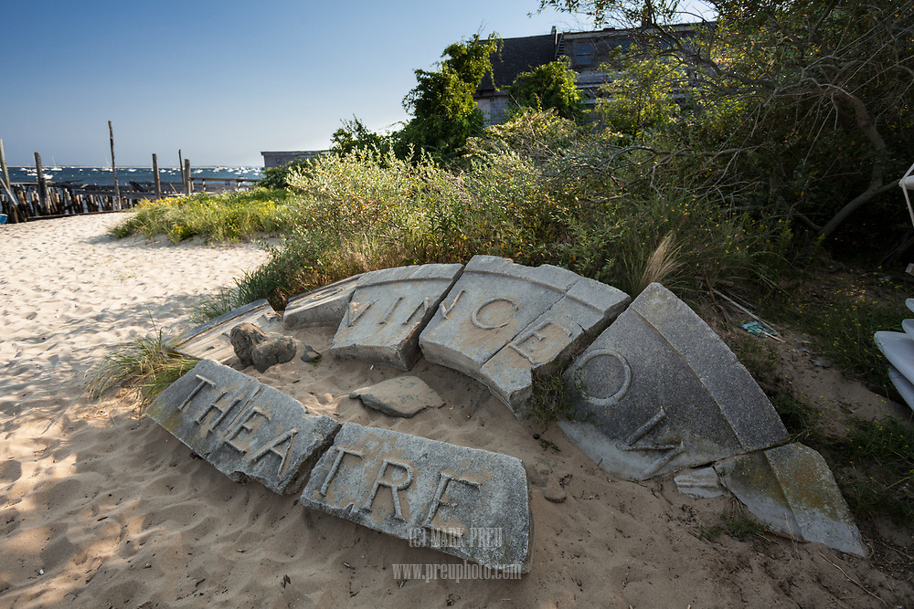 The stone sign for the old Provincetown Theatre lies on the beach behind Whaler's Wharf.