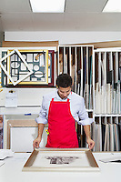 Young skilled worker adjusting frame on photograph