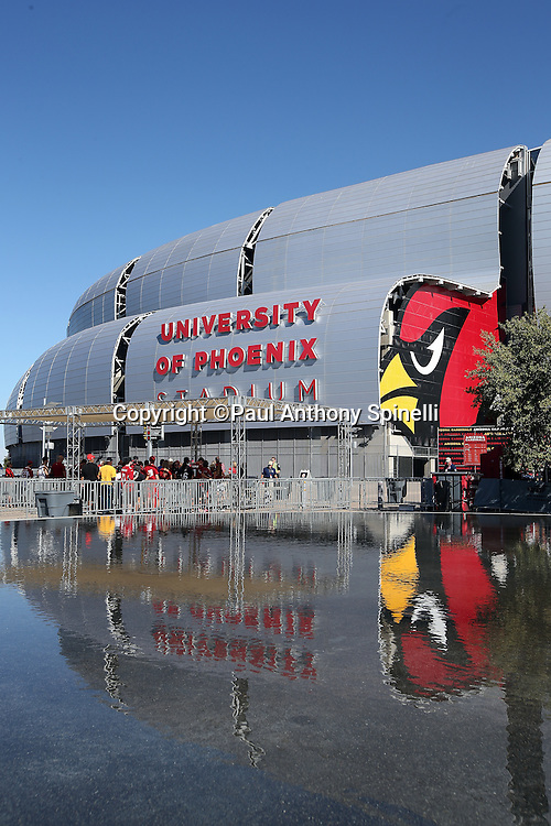 The Arizona Cardinals logo and the University of Phoenix Stadium are reflected in a fountain reflecting pool in this wide angle, general view photograph of the stadium exterior taken before the Arizona Cardinals 2015 NFL preseason football game against the San Diego Chargers on Saturday, Aug. 22, 2015 in Glendale, Ariz. The Chargers won the game 22-19. (©Paul Anthony Spinelli)