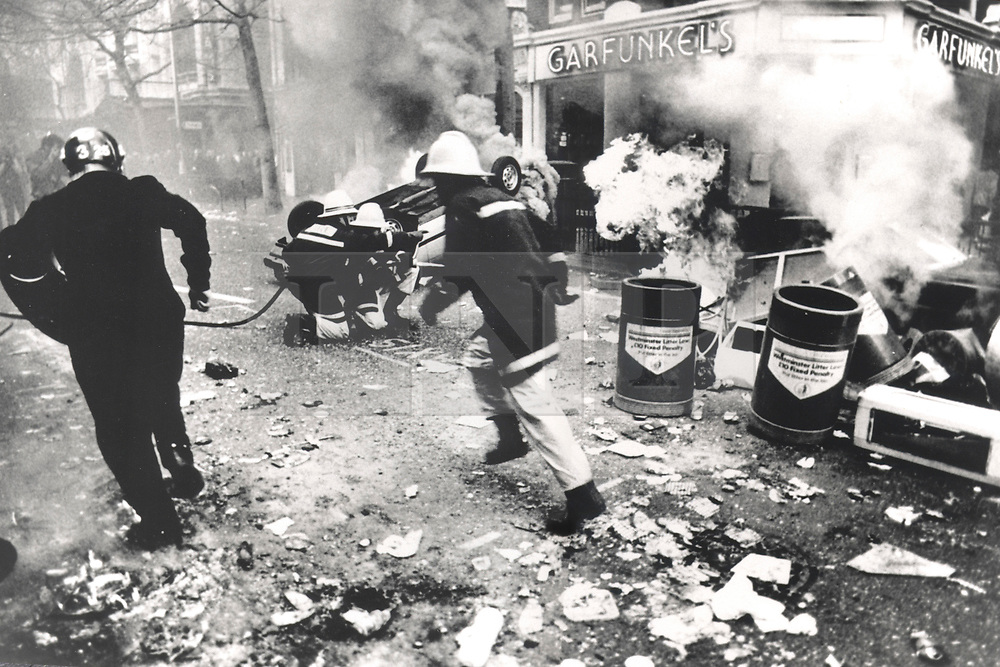 © Licensed to London News Pictures. 25/03/2020. London, UK. In this image from March 31st 1990 a police officer and a fire fighter run past burning cars on Charing Cross Road during the London poll tax riots. The protest on the last day of March in 1990 started peacefully when thousands gathered in a south London park to demonstrate against Margaret Thatcher's Government's introduction of the Community Charge - commonly known as the poll tax. Marchers walked to Whitehall and Trafalgar Square where violence broke out with the trouble spreading up through Charring Cross Road and on to the West End. Police estimated that 200,000 people had joined the protest and 339 were arrested. The hated tax was eventually replaced by the Council Tax under John Major's government in 1992.  Photo credit: Peter Macdiarmid/LNP
