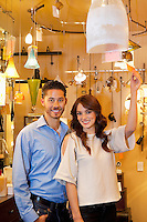 Portrait of a happy young couple with price tag in lights store