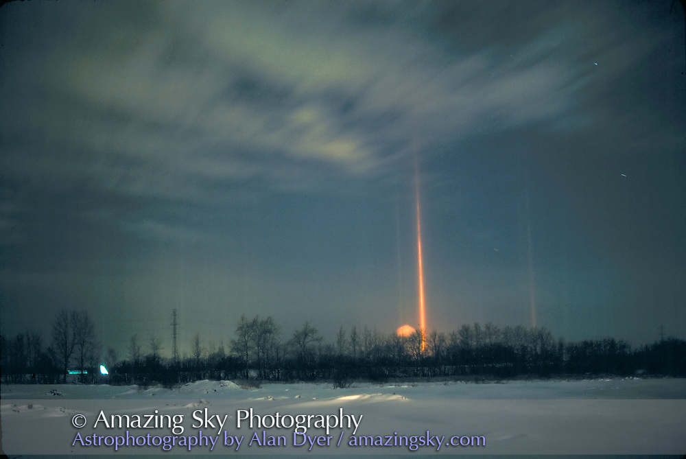 Light pillars caused by streetlight reflecting off floating flat ice crystals on a still, cold winter night. ..Taken from Edmonton, Alberta..Color corrected to remove green cast from Mercury vapour lights