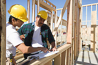 Construction workers reading blueprint on building site