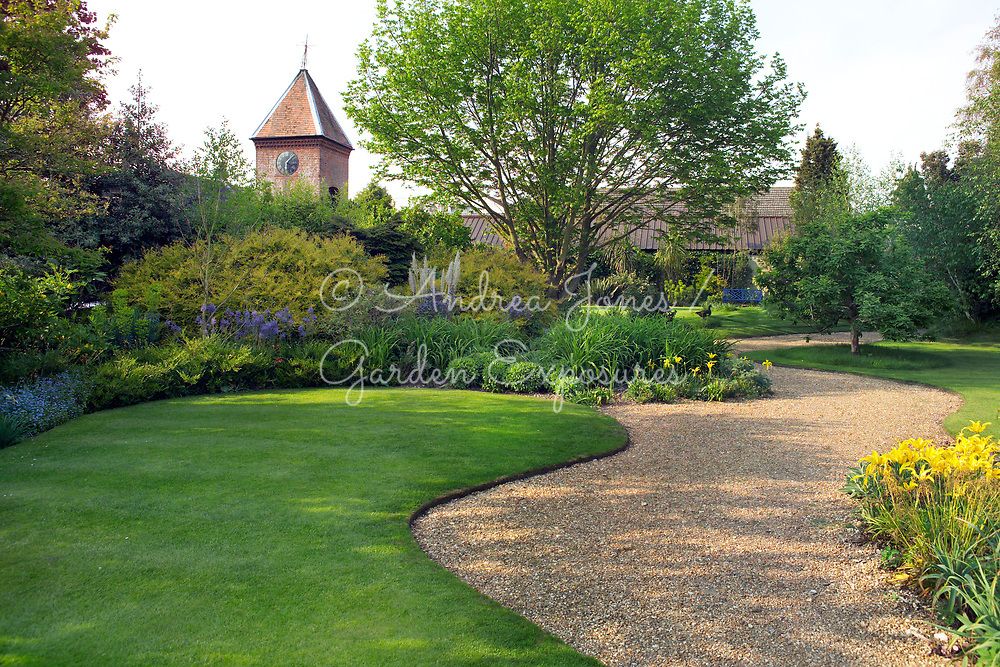 View to Clock House Garden, Denmans Garden with curving gravel paths, flowering borders, shrubs, trees and manicured lawn<br /> <br /> Denmans Garden, Chichester, West Sussex. <br /> Design by John Brookes