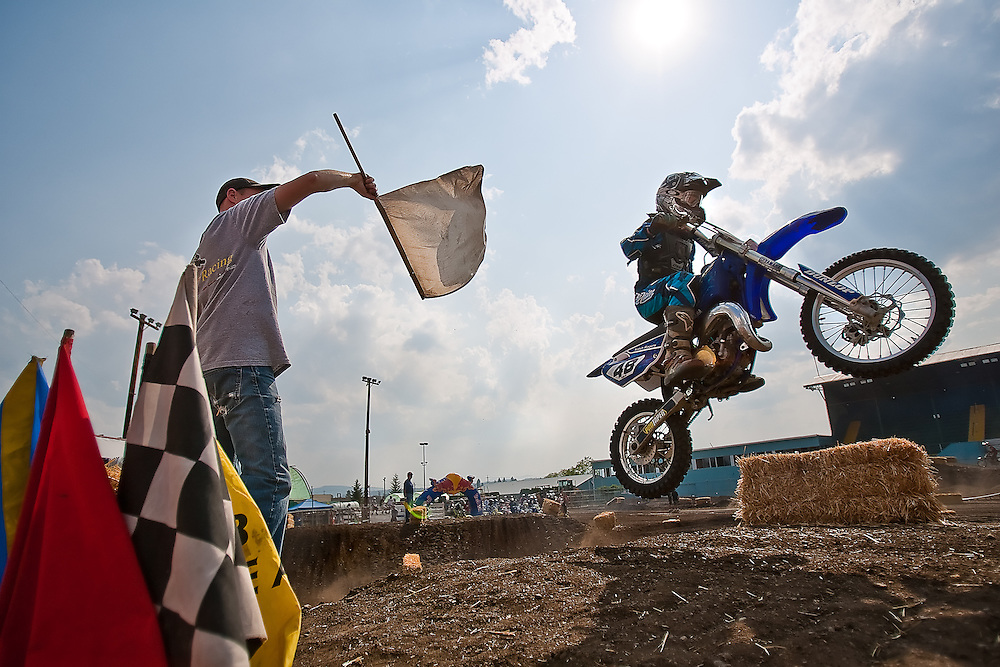 Kaleb Rogers, right, of Athol, flies over the table top jump on the motocross course at Kootenai County Fairgrounds on Friday as official announcer Bart McAllister, left, waves the white flag indicating the last lap during a practice run for motocross competitors.