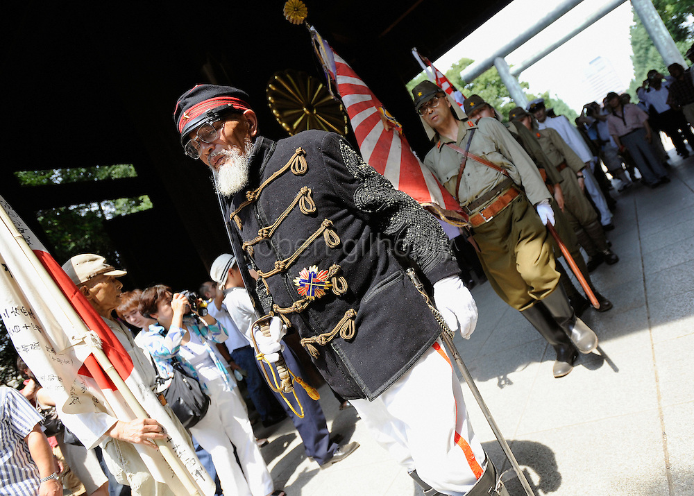 Dressed in Edo-period military garb, Hakugaku Kuribayashi, 80, leads a march to pray during a events to commemorate the anniversary of the end of World War II at Yasukuni Shrine in Tokyo, Japan on 28 Aug. 2008. Wartime prime minister Hideki Tojo - who ordered the attack on Peal Harbor and was charged and hanged as a war criminal after World War II, is enshrined inside the controversial Yasukuni Shrine together with 13 other convicted war criminals, a fact that still angers citizens in China and South Korea, both of which fell vicim to Japan's wartime activities. Aug 15. is the anniversary of Japan's surrender in World War II and 100s of thousands of pilgrims from around the country visit the shrine..Photographer: Robert Gilhooly