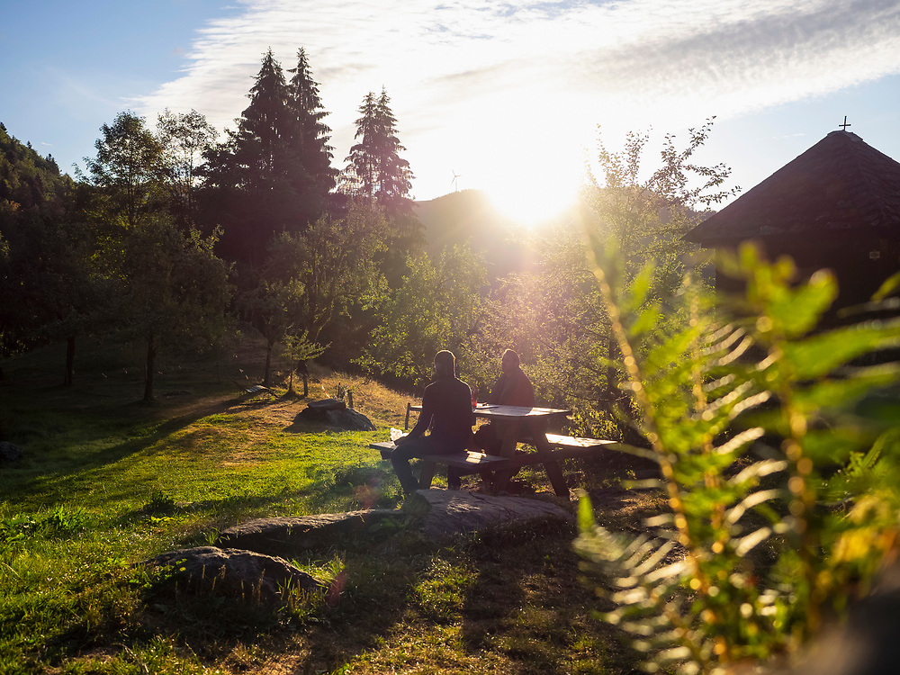 Silhouette of two male hiker relaxing on bench, Baden-Wuerttemerg, Germany