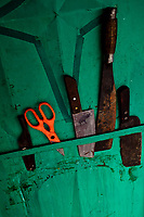 Rusty cooking knives and scissors on an iron door in a fishing boat in Vietnam.