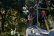 Workers remove a statue of Robert E. Lee from a public park in Dallas, Thursday, Sept. 14, 2017. (Cooper Neill for The Texas Tribune)