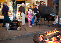 """Randy Bullerwell of Of My Life Jewelers treats Lila Miller, Katie Miller, Joshua Thomas, Elijah Miller and Jenn Miller to roasted chestnuts Friday evening during the """"Christmas in the Village"""" festivities in downtown Laconia.  (Karen Bobotas/for the Laconia Daily Sun)"""