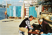 turks play backgammon in Kuzguncuk district with view of Bosforus bridge in the background