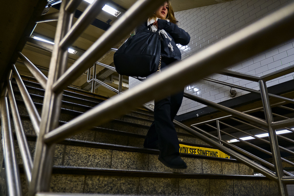 "Woman walking down subway steps past yellow sign reading ""you see something"""