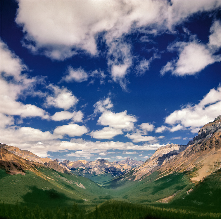 Puffy clouds shadow the green floor of a mountain valley, in Yoho National Park, British Columbia, Canada. ©Ric Ergenbright