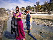 07 MARCH 2017 - KATHMANDU, NEPAL:  Women do their laundry in Bagmati River below the cremation ghats at Pashupatinath Temple, the oldest Hindu temple in Kathmandu. It is Nepal's most holy river, and this stretch of the river is like Varanasi in India. The river bank is lined with cremation ghats. Many Hindus, from both Nepal and India, make pilgrimages to Pashupatinath.    PHOTO BY JACK KURTZ