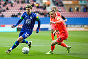 Wigan Athletic midfielder Josh Windass tackled by Huddersfield Town defender Florent Hadergjonaj during the EFL Sky Bet Championship match between Wigan Athletic and Huddersfield Town at the DW Stadium, Wigan, England on 14 December 2019.