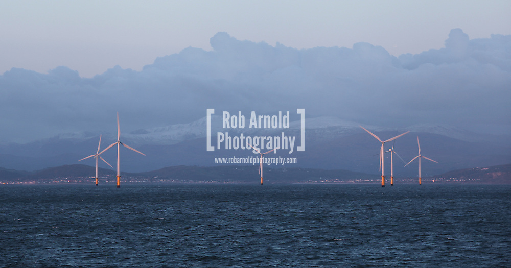 22/03/2014. North Wales, UK. The rising sun reflects off the turbines of the Rhyl Flats Offshore Wind Farm off the coast of North Wales this morning, 22nd March 2014. The snow capped hills of Snowdonia National Park can be seen in the distance. Photo credit : Rob Arnold