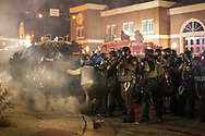 Police remove a bystander from the line of fire as tear gas canisters are deployed at demonstrators outside police headquarters in Ferguson, Mo., on Monday, November 24, 2014. Hundreds of protesters peacefully gathered earlier in the evening and when a grand jury announced its decision to not indict officer Wilson, most complied with police orders to disperse. Dozens remained, however, and began to throw rocks and bottles at police. Wide scale looting, arson and unrest followed.