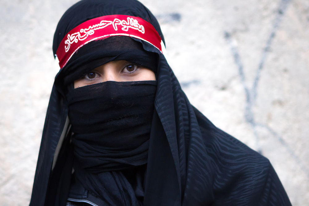 A shi'a muslim girl, wearing a black chador and veil, mourning during the Day of Ashura, on which shi'a muslims commemorate the martyrdom of Husayn ibn Ali, grandson of Muhammad, and third Shi'a imam (Bijar, Iran, 2012).<br />