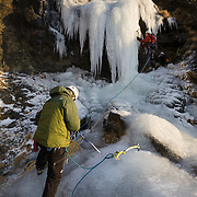 "Sveinn Eydal belaying Andri Bjarnasson climbing "" 55° "" WI 4 at Búahamrar, mt. Esja, Reykjavík, Iceland."