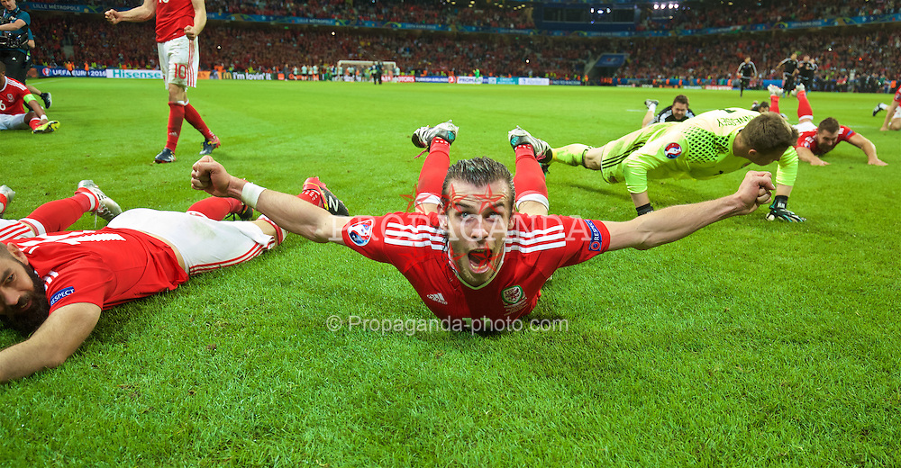 LILLE, FRANCE - Friday, July 1, 2016: Wales' Gareth Bale slides on the pitch as he celebrates after a 3-1 victory over Belgium and reaching the Semi-Final during the UEFA Euro 2016 Championship Quarter-Final match at the Stade Pierre Mauroy. (Pic by David Rawcliffe/Propaganda)