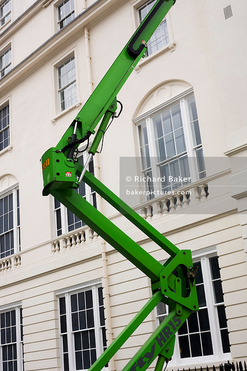 Green hydraulic crane stretches up to top floor of building in centralLondon.