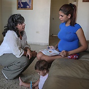 Judith Torres-Kilgore, who works with the Community Preparedness Office of Public Health Preparedness and Response at thePuerto Rico Department of Health visits with Kimberly Torres, 21, at Kimberly's apartment near Guayama, Puerto Rico. Kimberly is pregnant with her second child. Right now, Zika is spreading rapidly in Puerto Rico and pregnant women are at risk for becoming infected with Zika which can cause microcephaly and other birth defects. If the current trends continue, at least 1 in 4 people, including women who become pregnant, may become infected with Zika.