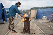 Calais, Pas-de-Calais, France - 16.10.2016    <br />     <br />  A refugee from parkistan boil water. &rdquo;Jungle&quot; refugee camp on the outskirts of the French city of Calais. Many thousands of migrants and refugees are waiting in some cases for years in the port city in the hope of being able to cross the English Channel to Britain. French authorities announced that they will shortly evict the camp where currently up to up to 10,000 people live.<br /> <br /> Ein Fluechtling aus Parkistan kocht Wasser. &rdquo;Jungle&rdquo; Fluechtlingscamp am Rande der franzoesischen Stadt Calais. Viele tausend Migranten und Fluechtlinge harren teilweise seit Jahren in der Hafenstadt aus in der Hoffnung den Aermelkanal nach Gro&szlig;britannien ueberqueren zu koennen. Die franzoesischen Behoerden kuendigten an, dass sie das Camp, indem derzeit bis zu bis zu 10.000 Menschen leben K&uuml;rze raeumen werden. <br /> <br /> Photo: Bjoern Kietzmann