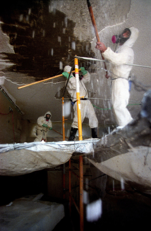 Crews remove asbestos from the ceiling of a high school classroom