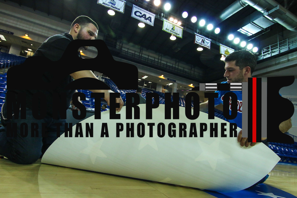 James Personti Jr. ,LEFT, and Jon Gleber, RIGHT, of unique Images of Wilmington Delaware place decal on the court in preparation for a Saturday NBA D-league regular season basketball game between the Delaware 87ers (76ers) and Springfield Armor (Brooklyn Nets) Friday, Apr. 04, 2014 at The Bob Carpenter Sports Convocation Center, Newark, DEL.