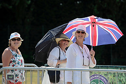 © Licensed to London News Pictures. 06/07/2018. LONDON, UK. Spectators from New Zealand queuing for day tickets in Wimbledon Park to the Wimbledon Tennis Championships shelter under an umbrella.  Temperatures forecast to approach 30C mean that the majority have taken precautions to protect themselves from the sun by wearing sunglasses and sunhats.  Photo credit: Stephen Chung/LNP