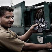"""Un trabajador """"Zabbaleen"""" muestra piezas de plástico inyectado que se usan en la construcción, producido con plástico reciclado en la planta de reciclaje de Katameya, que dirige la ONG A.P.E. en las afueras del Cairo. En medio del barrio de Manshiet Nasr a las afueras de El Cairo esta situado el asentamiento de Mokattam conocido como la """"Ciudad de la Basura"""" , está habitado por los Zabbaleen ,una comunidad de unos 45.000 cristianos coptos que viven desde hace varias décadas de reciclar los desperdicios que genera la capital egipcia: plástico, aluminio, papel y desechos órganicos que transforman en compost . La mayoría forman parte de la Asociación para la Protección del Ambiente (APE) una ONG que actúa en el área, cuyos objetivos son proteger el medio ambiente y aumentar el sustento de las recuperadores de basura de El Cairo. Según la ONU, el trabajo que se realiza en Mokattam como uno de los diez mejores ejemplos del mundo en el mejoramiento medioambiental. El Cairo , Egipto, Junio 2011. ( Foto : Jordi Camí )"""