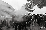 A man in a crowd of ravers waving a smoke flare, Upper chapel Rave, Brecon, Wales August 2016