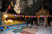 A golden reclining Buddha statue in the sunlight in a Killing Cave of Phnom Sampeau in Battambang region, Cambodia, South East Asia.  Next to the statue is a shrine containing skulls and bones from some of the victims who were killed thrown into these caves during the Khmer Rouge in 1970s. A Cambodian man sits in front of the statue making wrist band souvenirs.  (photo by Andrew Aitchison / In pictures via Getty Images)