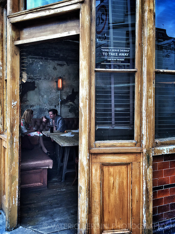 A couple enjoys a bottle of wine at The Sun Tavern in Bethnal Green Road. London UK