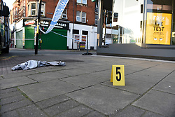 © Licensed to London News Pictures. 06/05/2018. LONDON, UK.  An evidence marker and a blood strewn hoodie on the ground near Palmerston Road in Wealdstone, near Harrow, north west London, following reports of two separate shooting incident around midday on Sunday 6 May 2018.  The two victims are a 12 year old boy and a15 year old boy.  Investigations are ongoing.  Photo credit: Stephen Chung/LNP