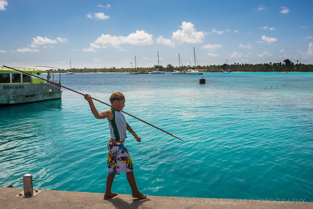 A young boy ready to throw his harpoon towards one of the fishes swimming in the shallow waters of Rangiroa lagoon.