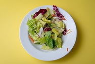 Mixed green salad in shallow white bowl on a yellow background.
