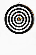 Dart board on white background with 2 yellow and two red darts around the centre