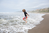 A boy jumps over waves on the beach at Lincoln, City Oregon