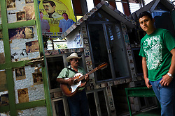 A man plays guitar in a chapel devoted to Jesus Malberde, as a youth in a shirt ofen associated with narco culture walks by, in Culiacan, Mexico.  Malverde is a folk saint worshipped by many people in the underworld and often associated with narcoculture and drug dealers. He is thought of as the Mexican version of Robin Hood, looking after those who have been forgotten by the Church and those involved in a life of crime.  People come to the chapel to show their respect and pray.