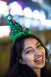 "© Licensed to London News Pictures . 16/12/2017. Manchester, UK. A woman wearing a Christmas tree hat at Deansgate Locks . Revellers out in Manchester City Centre overnight during "" Mad Friday "" , named for historically being one of the busiest nights of the year for the emergency services in the UK . Photo credit: Joel Goodman/LNP"