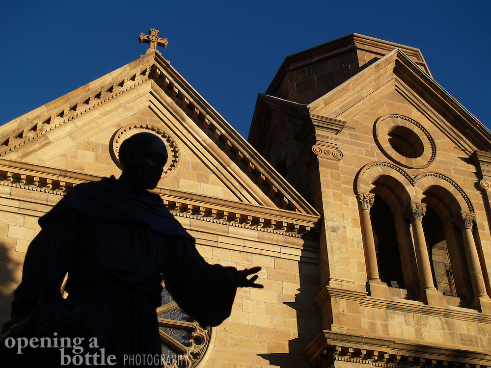 """A silhouette of the bronze St. Francis statue in front of the St. Francis Cathedral in Santa Fe, New Mexico. The site plays a key role in Willa Cather's """"Death Comes for the Archbishop."""""""