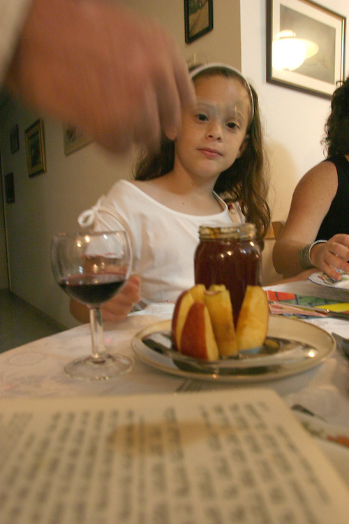 Neuhaus family celebrates the Rosh Hashana evening in a family diner at there home in Beer-Sheva at 22 September /2006 and eating apple with honey to make the coming year sweet.