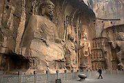 "The Longmen Grottoes (simplified Chinese: ????; traditional Chinese: ????; pinyin: lóngmén shíku?; lit. Dragon's Gate Grottoes) or Longmen Caves are one of the finest examples of Chinese Buddhist art. Housing tens of thousands of statues of Buddha and his disciples, they are located 12 kilometres (7.5 mi) south of present day Luòyáng in Hénán province, Peoples Republic of China. The images, many once painted, were carved into caves excavated from the limestone cliffs of the Xiangshan and Longmenshan mountains, running east and west. The Yi River flows northward between them and the area used to be called Yique (""The Gate of the Yi River"").[1][2][3] The alternative name of ""Dragon's Gate Grottoes"" derives from the resemblance of the two hills that check the flow of the Yi River to the typical ""Chinese gate towers"" that once marked the entrance to Luoyang from the south.[4].There are as many as 100,000 statues within the 1,400 caves, ranging from an 1 inch (25 mm) to 57 feet (17 m) in height. The area also contains nearly 2,500 stelae and inscriptions, whence the name ?Forest of Ancient Stelae"", as well as over sixty Buddhist pagodas. Situated in a scenic natural environment, the caves were dug from a 1 kilometre (0.62 mi) stretch of cliff running along both banks of the river. 30% date from the Northern Wei Dynasty and 60% from the Tang, caves from other periods accounting for less than 10% of the total.[3] Starting with the Northern Wei Dynasty in 493 AD, patrons and donors included emperors, Wu Zetian of the Second Zhou Dynasty, members of the royal family, other rich families, generals, and religious groups.[1][5].In 2000 the site was inscribed upon the UNESCO World Heritage List as ?an outstanding manifestation of human artistic creativity,? for its perfection of an art form, and for its encapsulation of the cultural sophistication of Tang China.[2]"