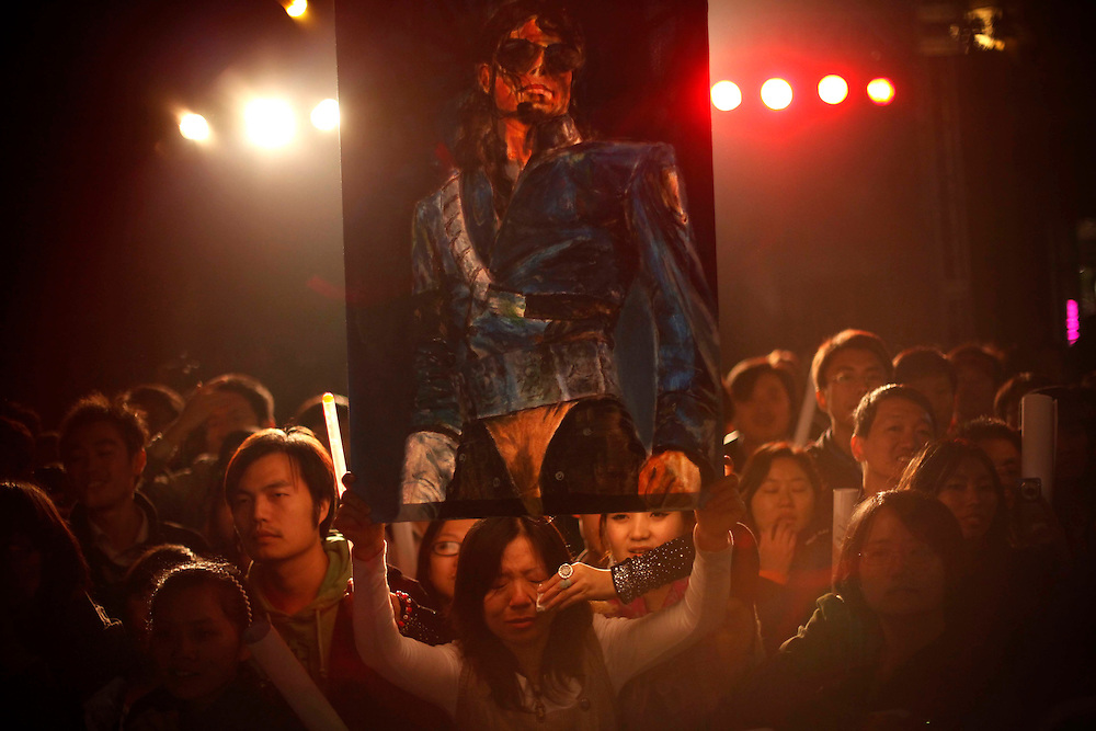 """A fan of Michael Jackson cries while holding a poster with his likeness ahead of the premiere of the documentary """"This Is It"""" in Beijing, China, Tuesday, Oct. 27, 2009.The Michael Jackson documentary """"This Is It"""" has snapped up one of the last of China's 20 annual foreign movie import slots. Chinese censors approved the film , clearing it in time for the global release date of Oct. 28."""