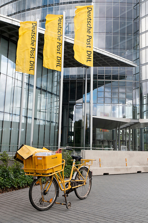 Ein  Fahrrad der Post vor dem Hauptsitz der Deutsche Post DHL in Bonn  |   bicycle of the Deutsche Post DHL in fron of the headquater in Bonn,Germany                                                 |