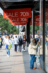 © Licensed to London News Pictures. 10/08/2018. London, UK. A woman peers through the window of House of Fraser's flagship store on Oxford Street in London after news that it had gone into administration. The department store chain has reportedly been bought by Sports Direct for £90m after administrators were appointed. Photo credit: Rob Pinney/LNP
