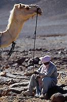 April 2001, Algeria --- Man Sitting Next to a Camel --- Image by © Owen Franken/CORBIS