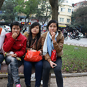 Young female Vietnamese teenagers relax on a park bench beside Hoan Kiem Lake, Hanoi, Vietnam, Hanoi is the capital of Vietnam and the country's second largest city. Hanoi, Vietnam. 17th March 2012. Photo Tim Clayton